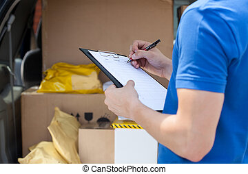 Courier's hand writing on clipboard - Close-up of a...