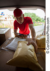 Courier taking parcel from car trunk - Young courier taking...