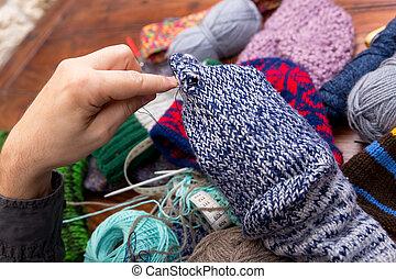 male hands darn wool socks - closeup of male hands darn wool...