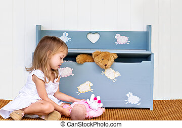 Child near toy chest - Child playing with her doll while a...
