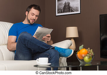 Man sitting on sofa relaxed and smiling. guy reading...