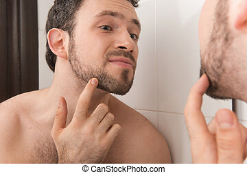 Closeup of young man examining his stubble in mirror Man...