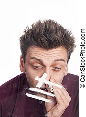 Young man sniffing cocaine from glass. close up of man snorting cocaine lines