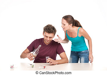 Man drinking alcohol and woman shouting at him. Photo of...