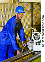 man operating lathe machine - african man operating a lathe...