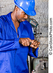 industrial worker - young african man doing metal work