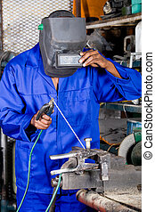 welder at work - african man using welding equipment