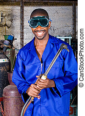 african welder - african man smiling with welding goggles on