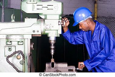 industrial worker - african man using heavy precision drill