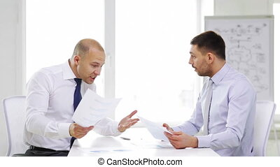 two serious businessmen with charts in office - business,...