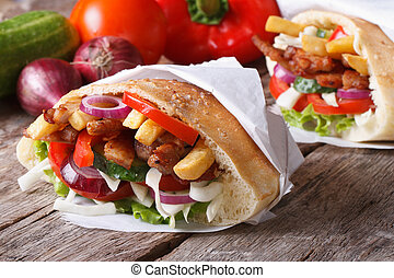 Doner kebab with meat and vegetables in pita wrapped in...