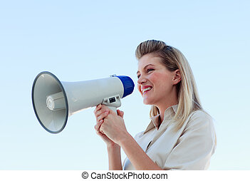 Businesswoman shouting through megaphone outdoors