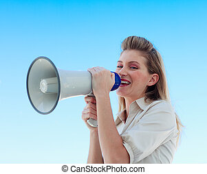 Beautiful businesswoman shouting through megaphone outdoors
