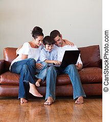 Happy family using a laptop  on a couch