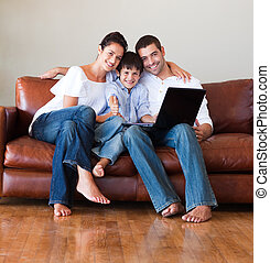Family using a laptop with thumbs up - Happy family using a...