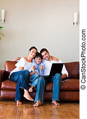 Family using a laptop with thumbs up on a couch