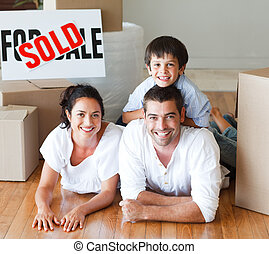 Family on the floor smiling at the camera after buying house