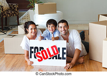 Happy family lying on the floor after buying house - Happy...