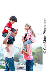 Parents giving their children piggyback rides - Young...