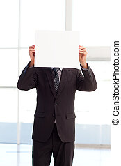 Man holding a big business card in front of his face in...