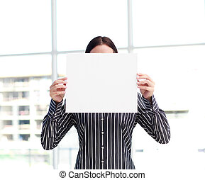 Smiling woman showing a big business card in front of her...