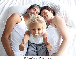 Happy little girl on bed with thumbs up and her parents -...
