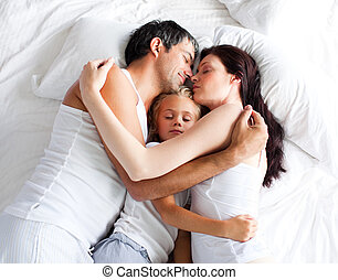 Little gril sleeping on bed with her parents at home