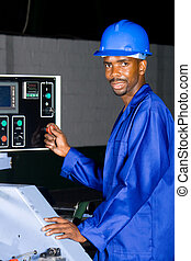 factory worker - man operating control panel in industrial...