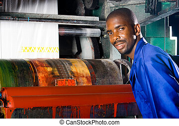 printing press worker - man checking the printing press in...