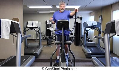 elliptical machine - mature man exercising on an elliptical...
