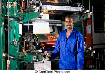african man operating printing press - industrial worker...