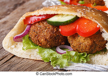 falafel with fresh vegetables in pita bread close-up on...