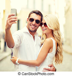 smiling couple taking selfie with smartphone - summer...
