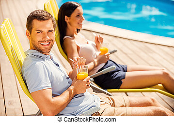 Enjoying their leisure time together. Side view of beautiful young couple sitting at the deck chairs by the pool and drinking cocktails while man looking at camera and smiling