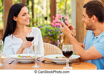 Smile for the camera! Handsome young man taking picture of her beautiful girlfriend with smart phone while relaxing in outdoors restaurant together