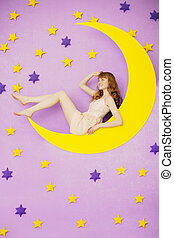 Girl sitting on the moon toy - Beautiful girl sitting on the...