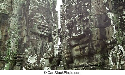 Huge stone faces on the walls of an ancient temple. Cambodia, Bayon