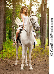 Young woman on a horse. Horseback rider, woman riding horse...