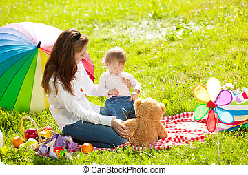 Beautiful Mom and baby outdoors. Happy family playing in...