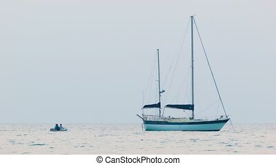 People arrived at the yacht that is anchored in the sea -...