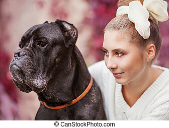 Portrait of a young girl hugging a big dog Cane Corso