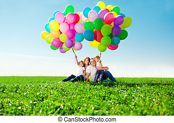 Happy family holding colorful balloons. Mom, ded and two...
