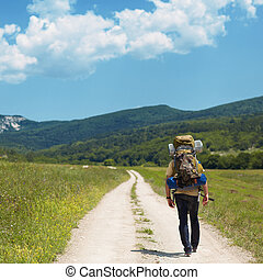 Tourist with a backpack and mountain panorama