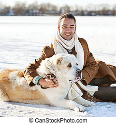 Man and central Asian shepherd walk in the park