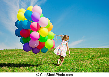 Little girl holding colorful balloons. Child playing on a...