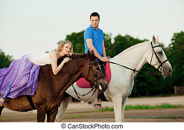 Two riders on horseback at sunset on the beach. Lovers ride...