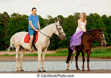 man and woman with a horses at the sea. Romantic love. - Two...