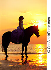 Beautiful woman riding a horse at sunset on the beach. Young...