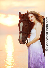 Beautiful woman riding a horse at sunset on the beach Young...