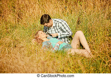 Happy young adult couple in love on the field. Two, man and...